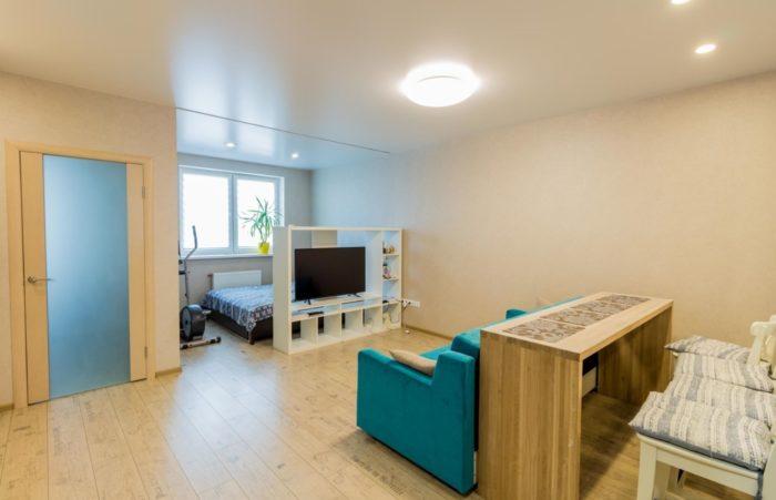 Зонирование квартиры студии с кроватью и диваном