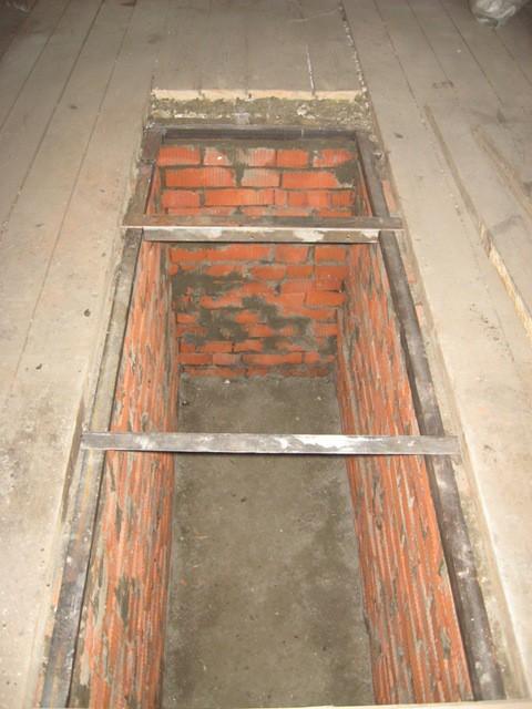 Металлический уголок, уложенный на стенки смотровой ямы