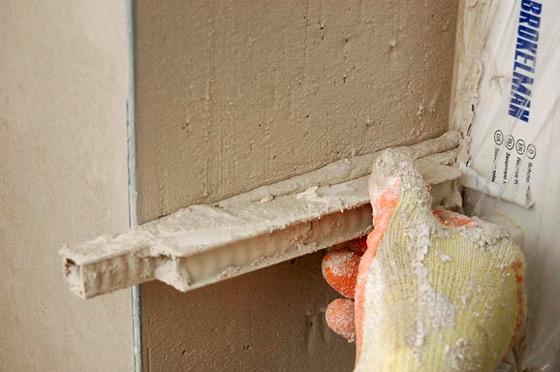 Разравнивайте и удаляйте излишки шпаклевки с помощью деревянной рейки