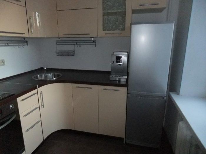 Угловая кухня с холодильником возле окна