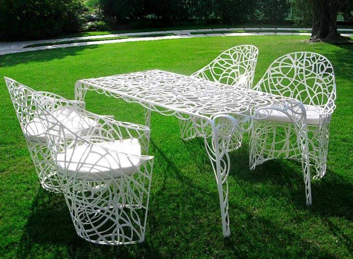 Кованая мебель тоже отлично впишется в ландшафт участка. Чтобы на ней было комфортно сидеть, используйте мягкие подушки и коврики