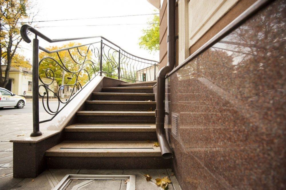 Металлическое ограждение прекрасно сочетается с гранитной лестницей
