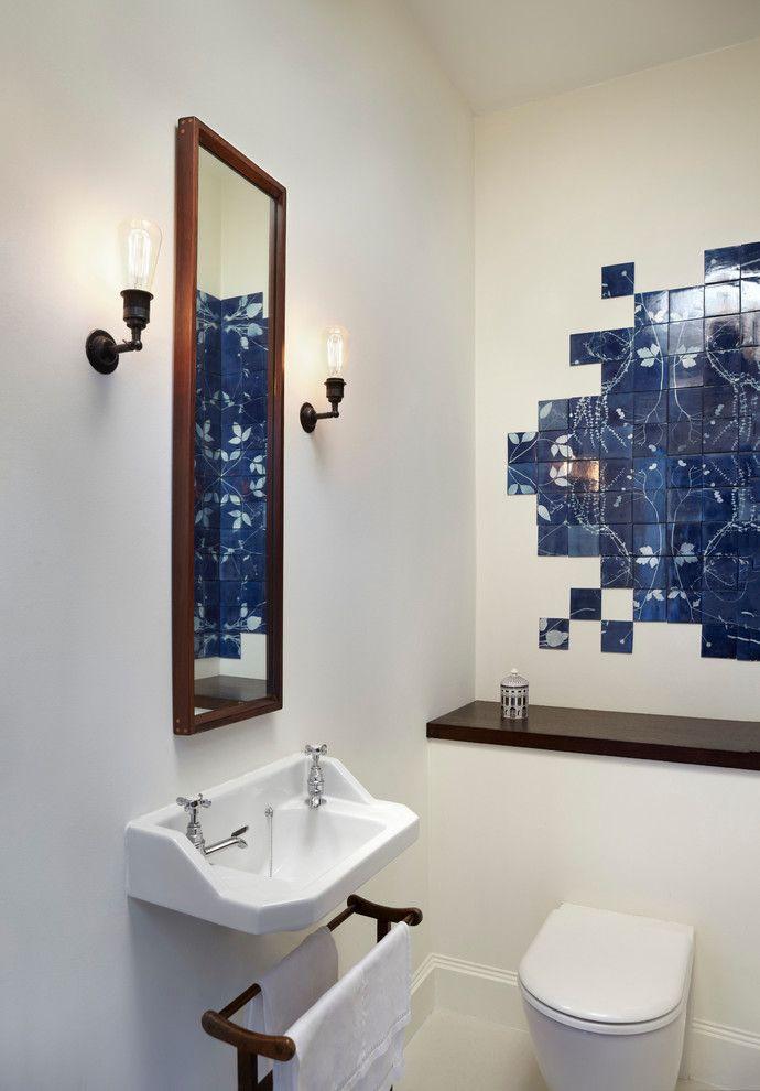 Панно из темно-синей плитки контрастирует на фоне белой ванной