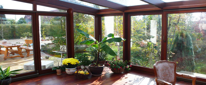 Зимний сад с каркасом на основе дерева и с обшивкой из стекла