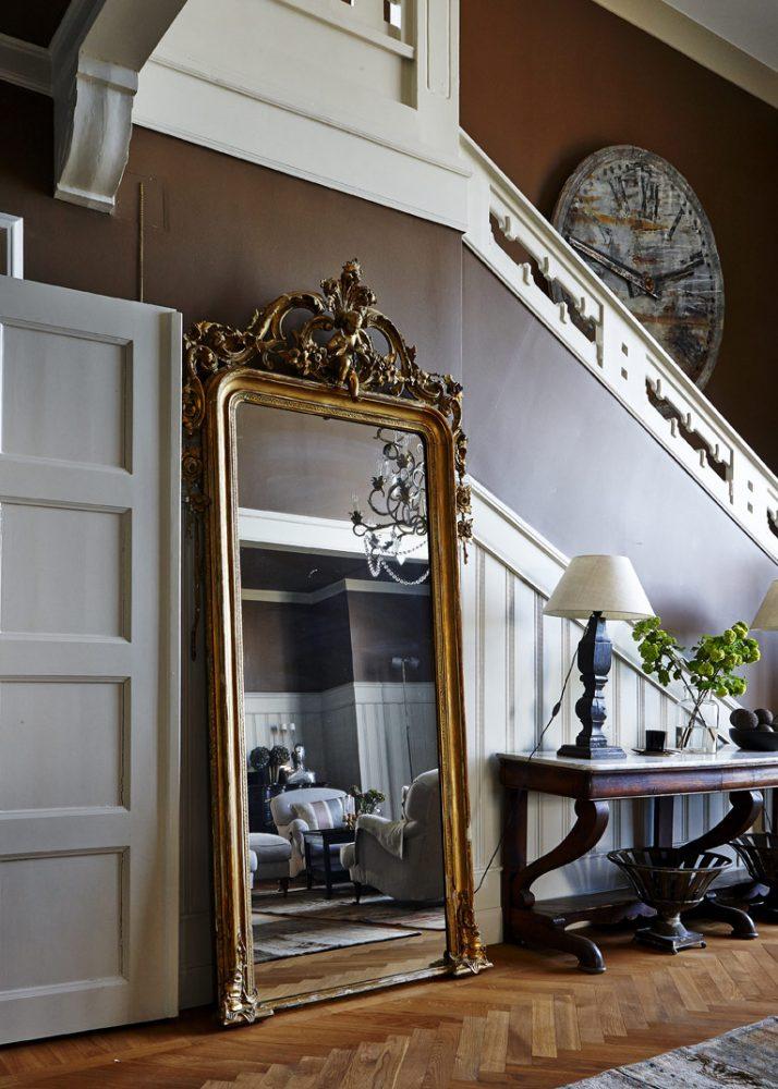 Красивое винтажное большое зеркало в прихожей, установленное на полу