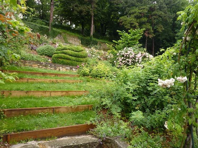 Склон садового участка с деревянными террасами