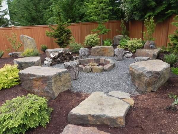 Дизайн маленького двора частного дома с большими камнями