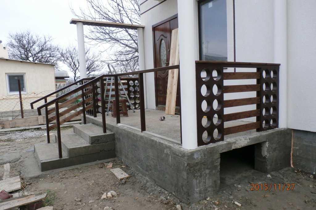 Один из вариантов бетонного крыльца с деревянными перилами