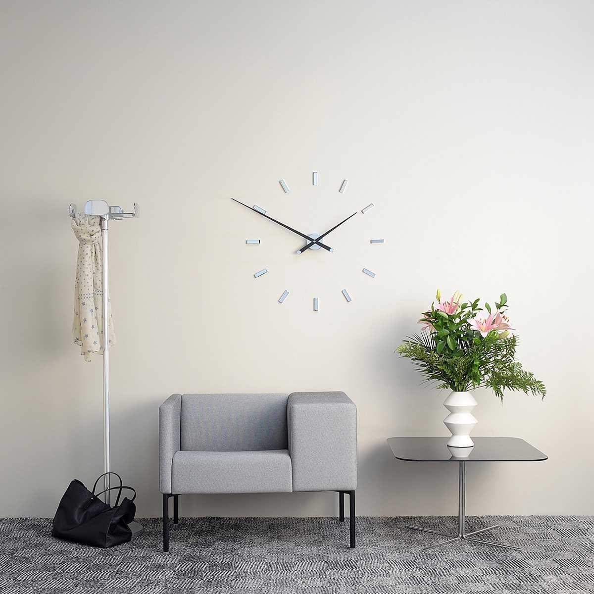 современный дизайн гостиной комнаты с необычными настенными часами