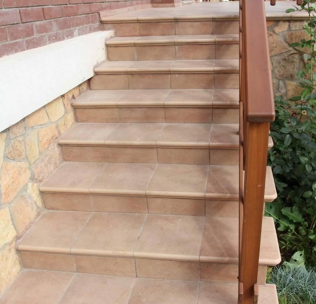 Облицовка ступеней лестницы плиткой в сочетании с деревянными перилами