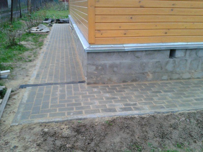 Отмостка вокруг дома из тротуарной плитки со швами, заполненными цементно-песчаной смесью