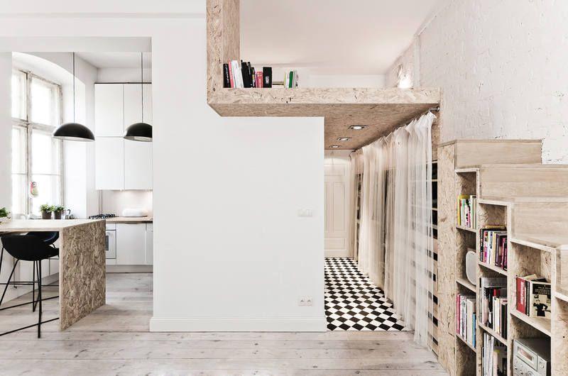 При организации второго уровня в небольшой студии можно использовать пространство под лестницей для хранения книг и одежды