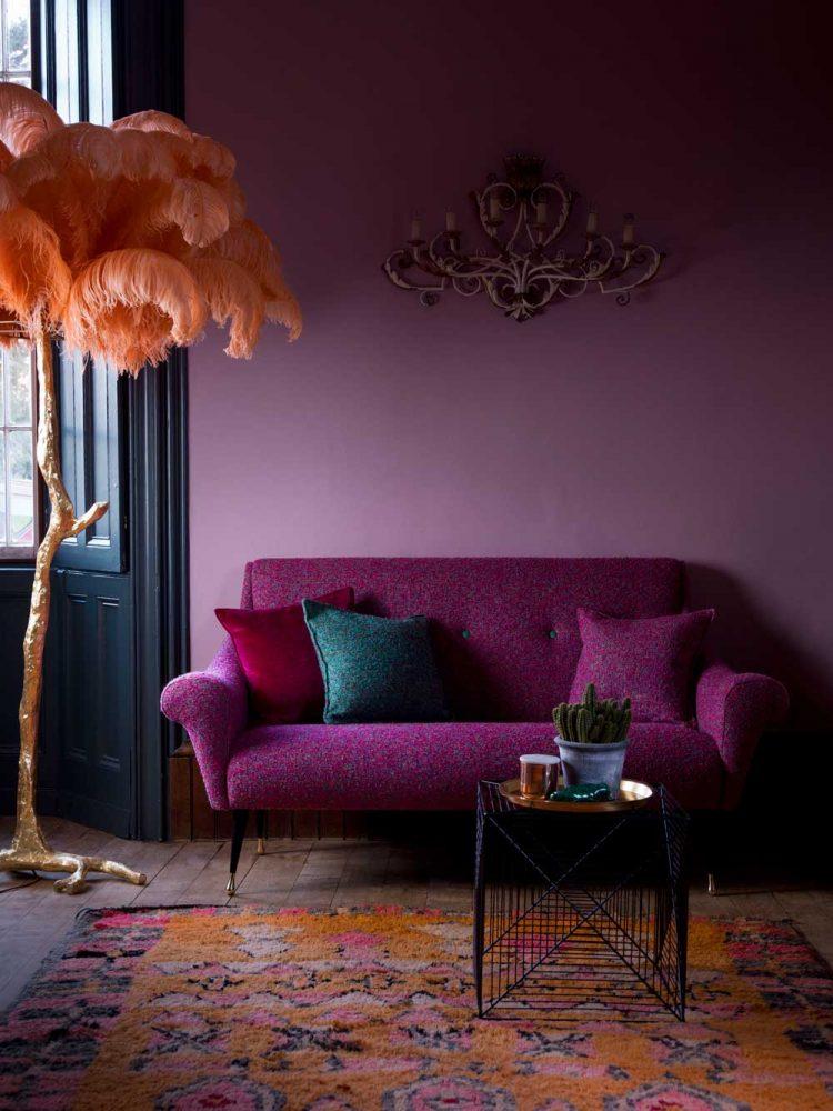 Уютная гостиная с сиреневыми обоями в пастельных тонах и ярким акцентом на комфортном диванчике