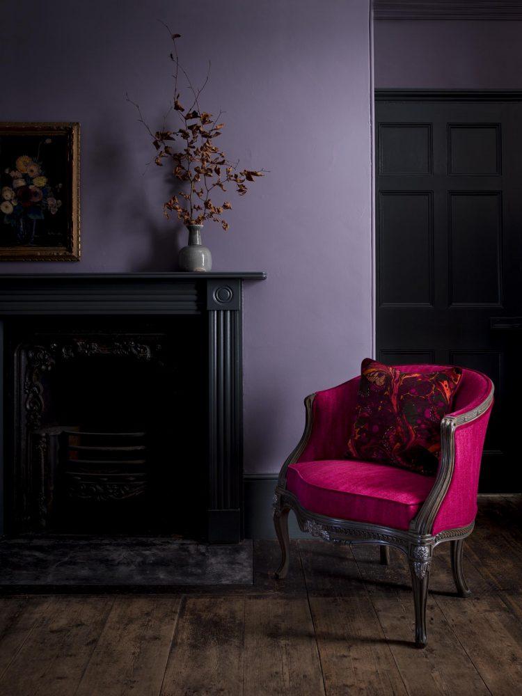 Темные пастельные сиреневые обои с серым оттенком в гостиной с ярким акцентом на ярко розовом клесле, исполненом в общем настроении комнаты