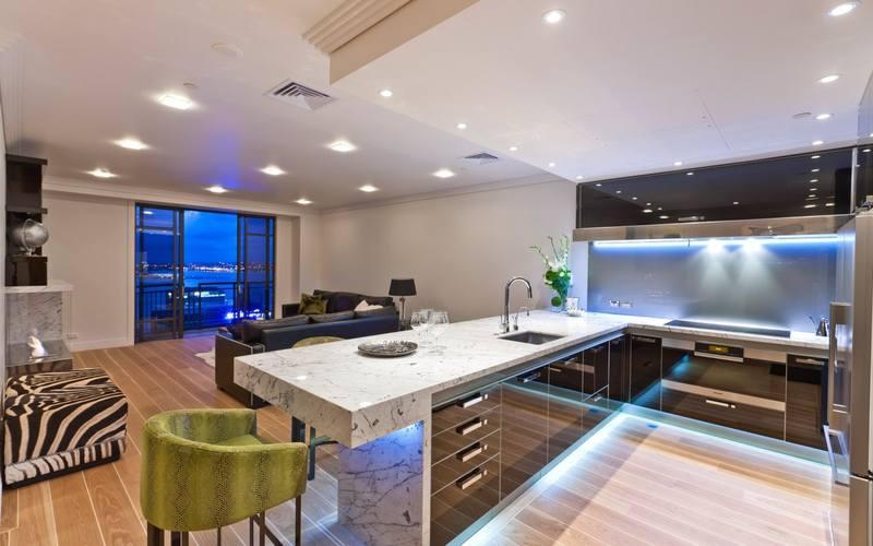 Точечные светильники в потолке над рабочей зоной кухни