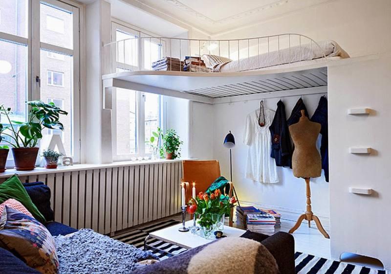 В студии с высоким потолком можно поднять спальное место, тем самым освободив дополнительное пространство для гардероба