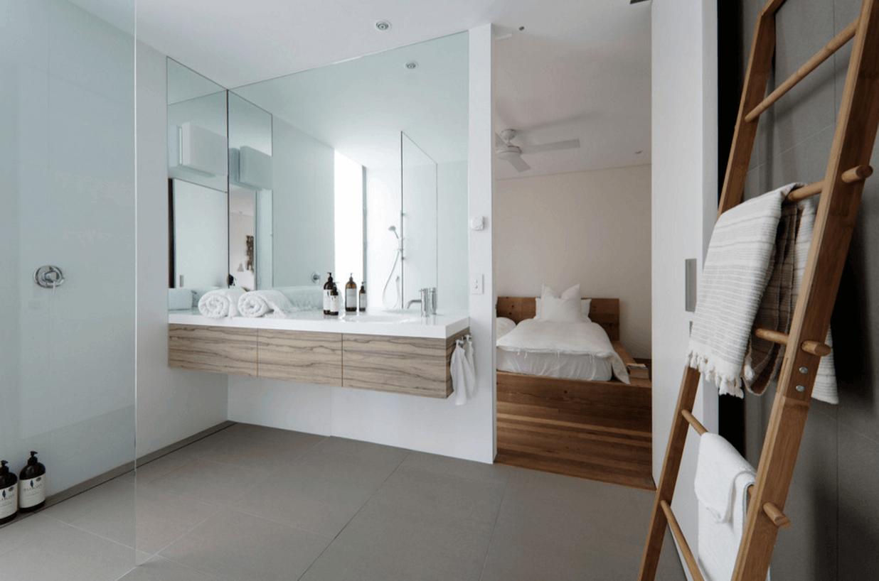 Большое зеркало над тумбой в интерьере светлой ванной комнаты