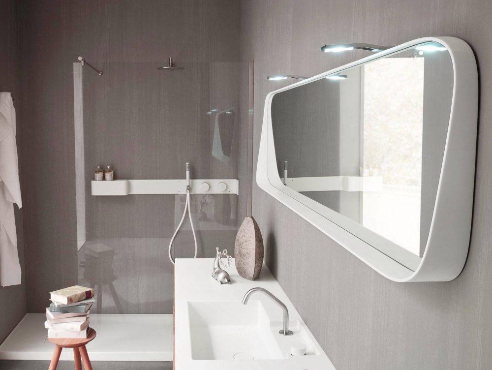Две точечных лампы подсвечивают креативной формы зеркало